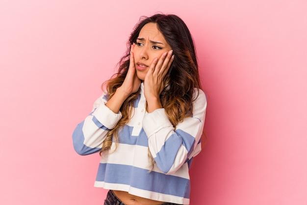 Młoda meksykańska kobieta na białym tle na różowej ścianie przestraszona i przestraszona.