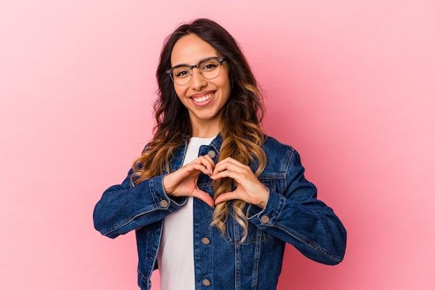 Młoda meksykańska kobieta na białym tle na różowym tle, uśmiechając się i pokazując kształt serca rękami.