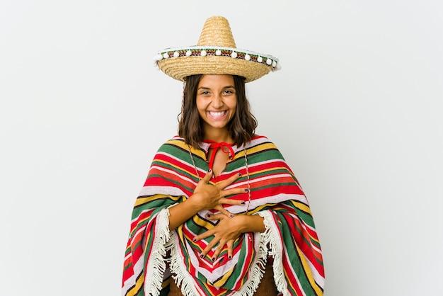 Młoda meksykańska kobieta na białym tle śmieje się radośnie i bawi się trzymając ręce na brzuchu.