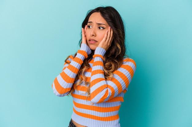 Młoda meksykańska kobieta na niebieskim tle przestraszona i przestraszona.