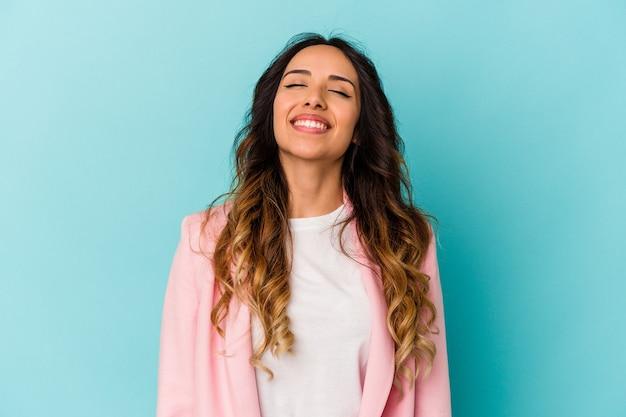 Młoda meksykańska kobieta na niebieskim tle śmieje się i zamyka oczy, czuje się zrelaksowana i szczęśliwa.