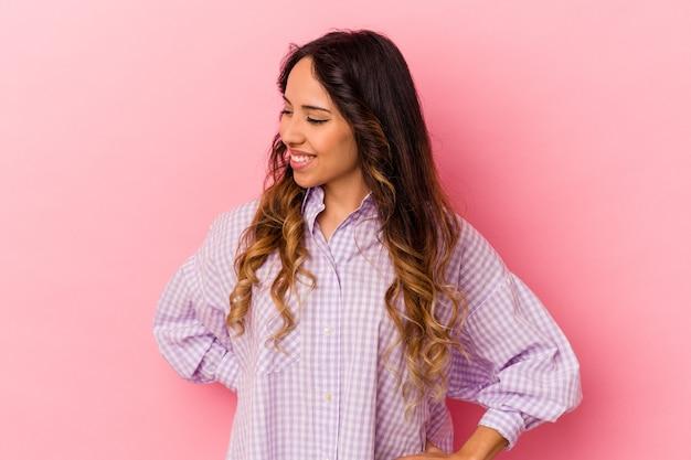 Młoda meksykańska kobieta na różowym tle śmieje się i zamyka oczy, czuje się zrelaksowana i szczęśliwa.