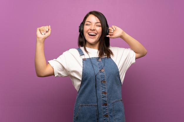 Młoda meksykańska kobieta nad odosobnionym słuchaniem muzyka z hełmofonami