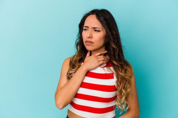 Młoda meksykańska kobieta odizolowana na niebieskiej ścianie cierpi na ból gardła z powodu wirusa lub infekcji.