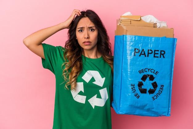 Młoda meksykańska kobieta recykling kartonu na białym tle na różowym tle, będąc w szoku, przypomniała sobie ważne spotkanie.