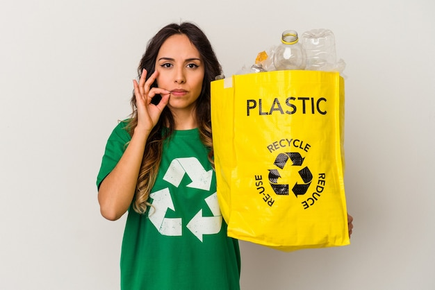 Młoda meksykańska kobieta recyklingu plastiku na białym tle z palcami na ustach, zachowując tajemnicę.