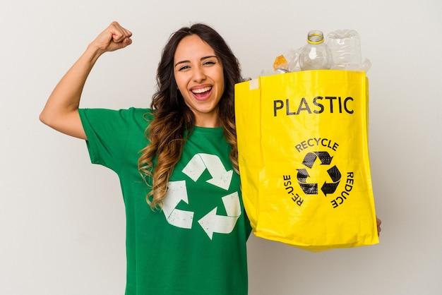 Młoda meksykańska kobieta recyklingu tworzyw sztucznych na białym tle podnosząc pięść po zwycięstwie, koncepcja zwycięzcy.