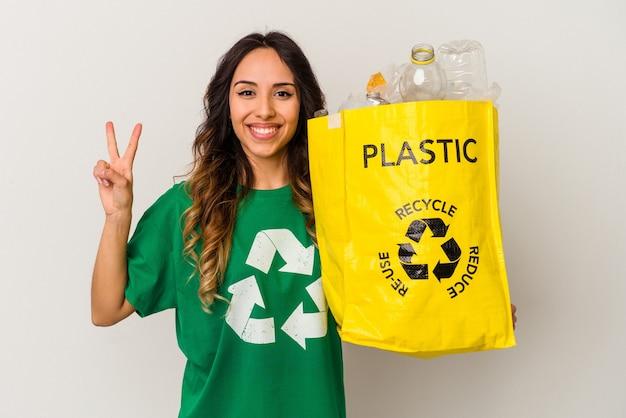 Młoda meksykańska kobieta recyklingu tworzyw sztucznych na białym tle pokazując numer dwa palcami.
