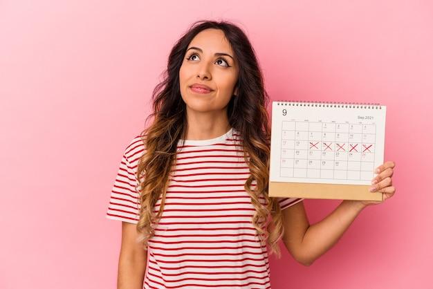 Młoda meksykańska kobieta trzyma kalendarz na białym tle na różowym tle marzy o osiągnięciu celów i zamierzeń
