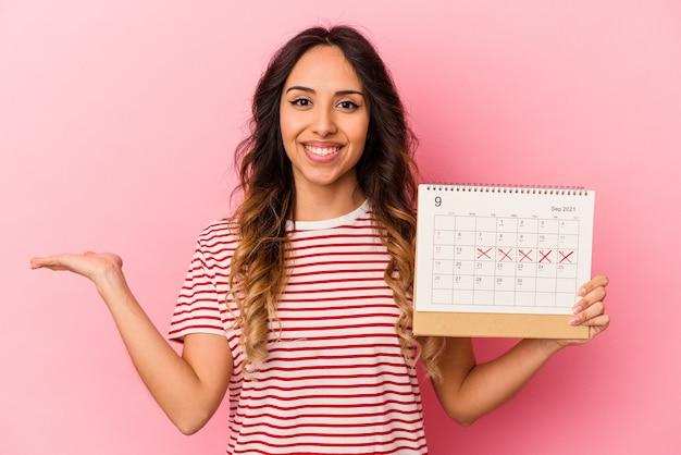 Młoda meksykańska kobieta trzyma kalendarz na białym tle na różowym tle pokazując miejsce na kopię na dłoni i trzymając drugą rękę na talii.