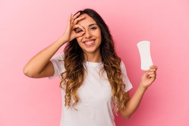 Młoda meksykańska kobieta trzyma kompres na białym tle na różowym tle podekscytowany utrzymując ok gest na oko.
