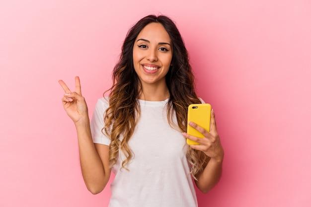 Młoda meksykańska kobieta trzyma telefon komórkowy na białym tle na różowym tle radosna i beztroska pokazująca palcami symbol pokoju.