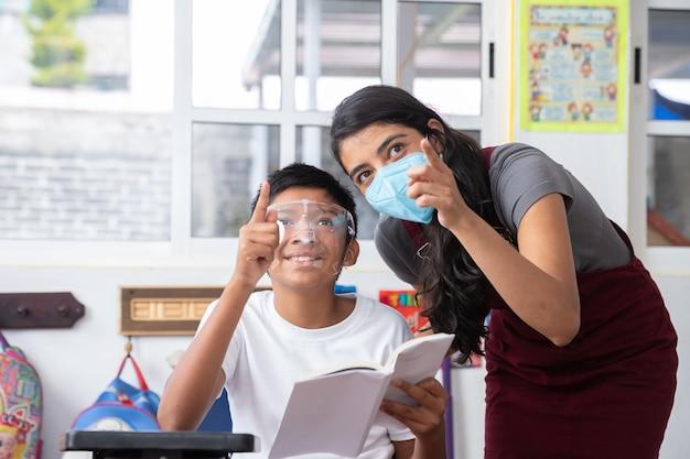 Młoda meksykańska nauczycielka i dziecko w klasie, noszenie maski, koncepcja edukacji przedszkolnej