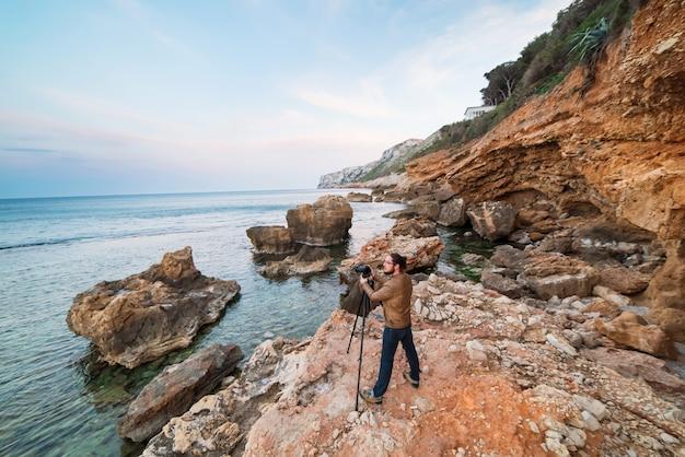 Młoda męska fotograf pozycja na skałach z tripod i robić fotografiom morze