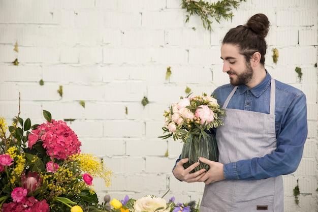 Młoda męska kwiaciarnia trzyma kwiat wazę przeciw białemu ściana z cegieł
