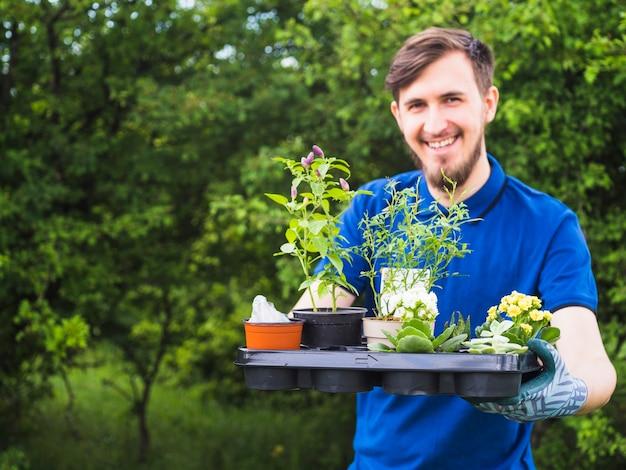 Młoda męska ogrodniczka mienia skrzynka z żywymi doniczkowymi roślinami w ogródzie