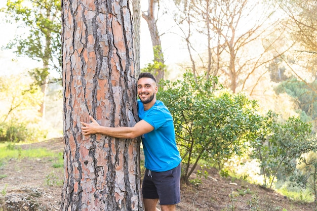 Młoda męska pozycja w drewnach i przytulenia drzewie