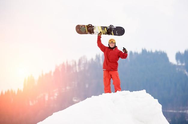 Młoda męska snowboarder pozycja na wierzchołku śnieżny wzgórze