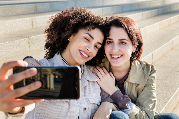 Młoda międzyrasowa para dziewczyn robi selfie
