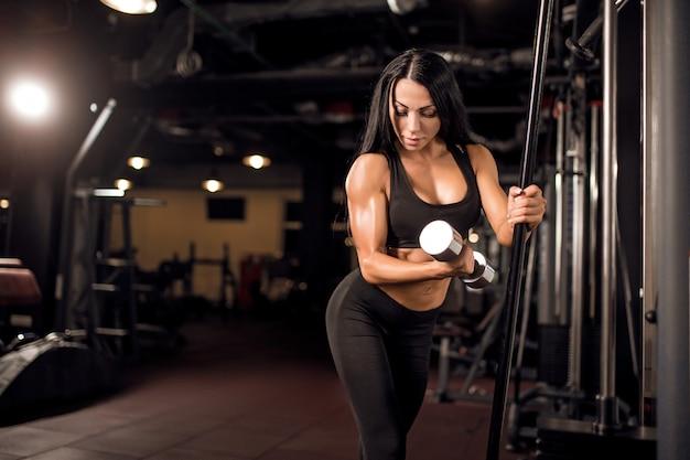 Młoda mięśniowa kobieta robi treningowi przy gym