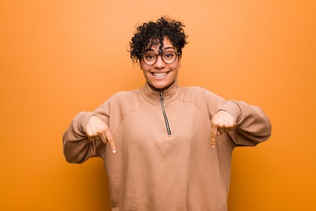 Młoda mieszana amerykanin afrykańskiego pochodzenia kobieta przeciw brown ścianie wskazuje palcami w dół, pozytywne uczucie.