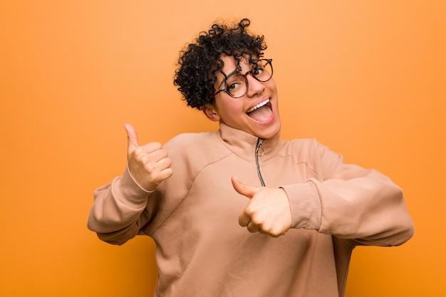 Młoda mieszana amerykanin afrykańskiego pochodzenia kobieta przy brown ścianą podnosi oba aprobaty, uśmiechnięty i pewny siebie.