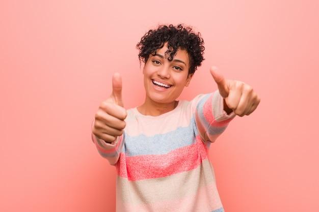 Młoda mieszana amerykanin afrykańskiego pochodzenia nastolatka kobieta z kciukami do góry, okrzyki o coś, wsparcie i szacunek.