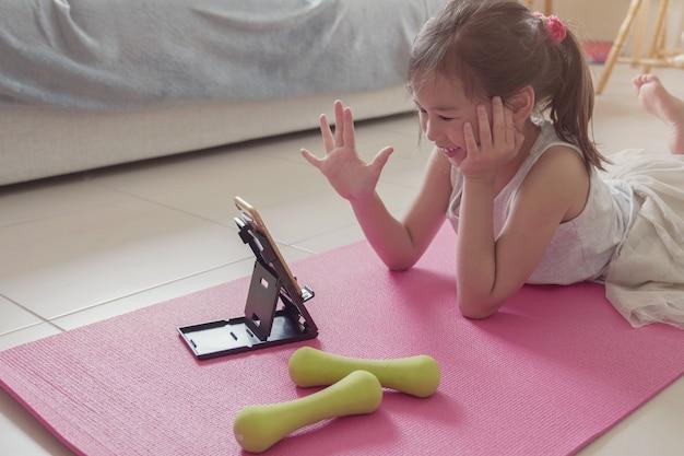 Młoda mieszana azjatycka dziewczyna ogląda streaming wideo na laptopie, trening trenuje w domu, przybliża ćwiczenia online klasę, ogólnospołeczny dystansowy pojęcie