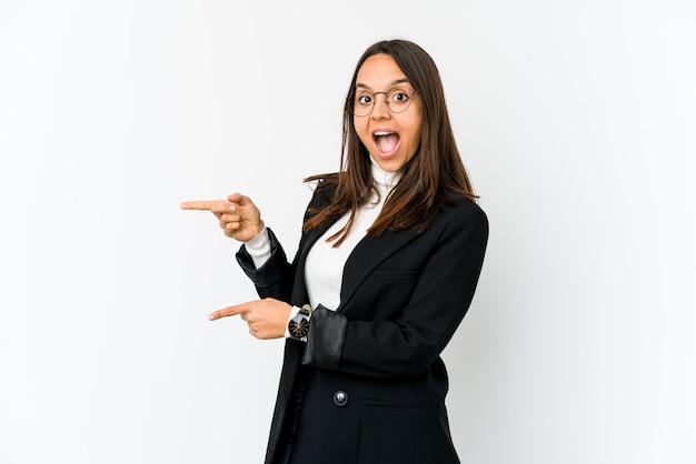 Młoda mieszana biegowa biznesowa kobieta odizolowywająca na białym podekscytowanym wskazywać z palcami wskazującymi daleko od.