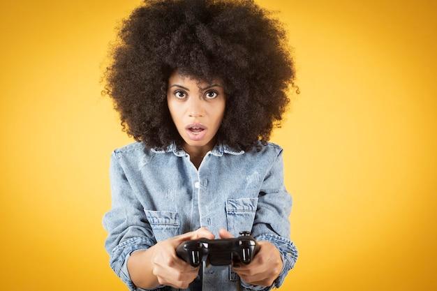 Młoda mieszana kobieta afroamerykanów, grając w gry wideo z zaskoczoną twarzą