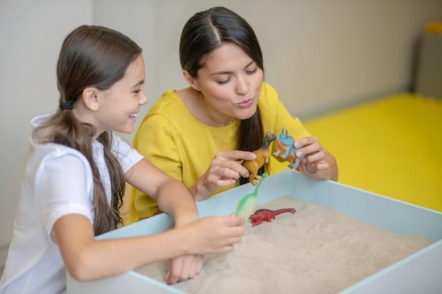 Młoda miła emocjonalna kobieta z miniaturowymi figurkami dinozaurów i radosna dziewczyna w pokoju zabaw