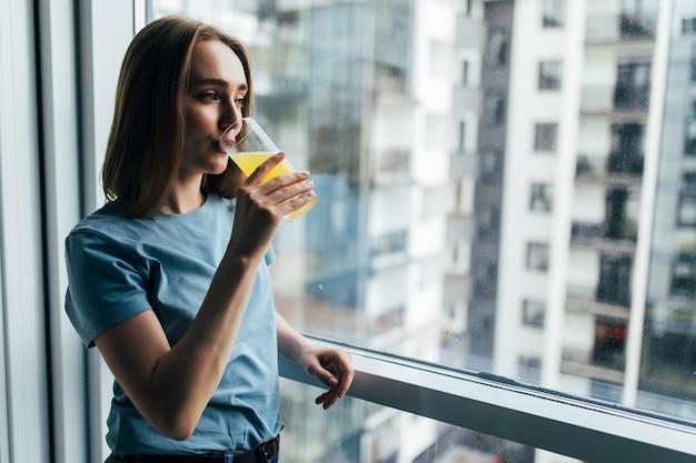 Młoda miła kobieta pije świeży sok, patrząc na okno w pomieszczeniu