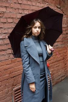 Młoda miła ładna dziewczyna w szarym płaszczu i golfie pozuje z parasolem