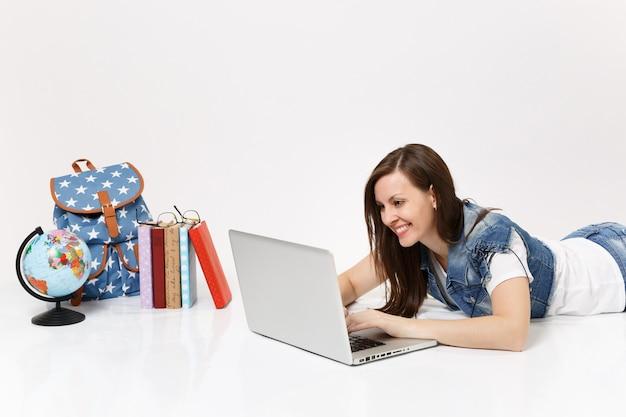 Młoda miła studentka w dżinsowych ubraniach, pracująca na komputerze typu laptop, leżąca w pobliżu kuli ziemskiej, plecak, podręczniki szkolne na białym tle