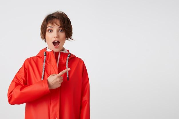 Młoda miła, szczęśliwa i zdumiona krótkowłosa dama w czerwonym płaszczu przeciwdeszczowym, z szeroko otwartymi ustami, słyszy fajne wieści. chce zwrócić twoją uwagę, wskazuje palcem na miejsce na kopię. na stojąco.