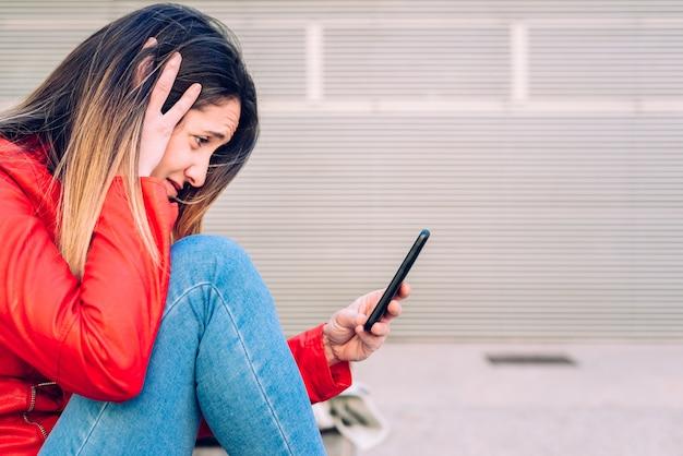 Młoda millennial studencka kobieta z smutną twarzą gdy konsultujący jej smartphone