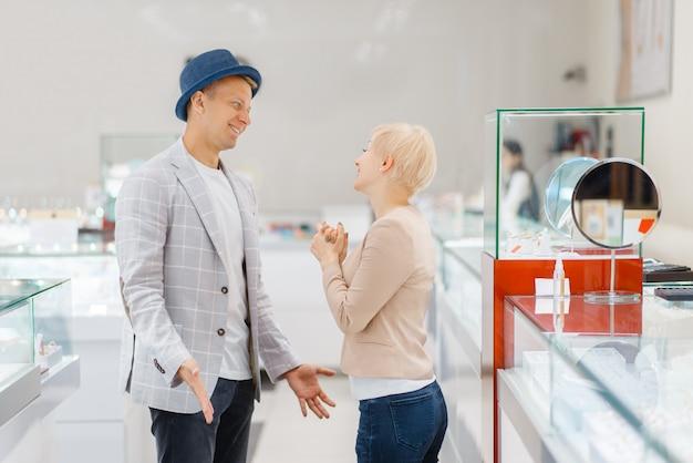 Młoda miłość para kupuje klejnoty w sklepie jubilerskim mężczyzna i kobieta wybiera obrączki ślubne. przyszła panna młoda i pan młody w sklepie jubilerskim