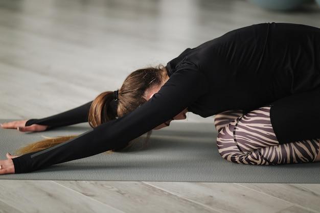 Młoda mistrzyni jogi nagrywa wideo z ćwiczeniami na kurs online z telefonem na statywie. lekkoatletyczne szkolenie kobiet w studio.