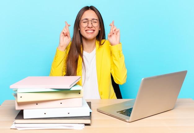 Młoda młoda bizneswoman uśmiecha się i niespokojnie krzyżuje oba palce, czuje się zmartwiona i marzy lub ma nadzieję na szczęście