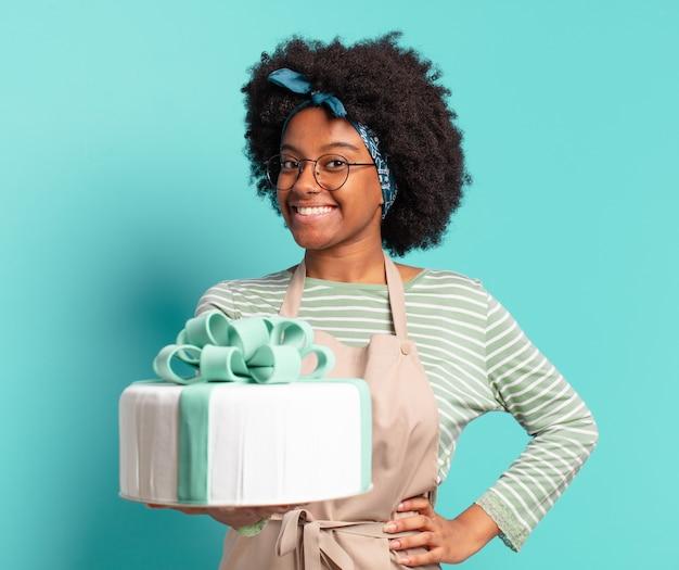 Młoda młoda kobieta piekarz afro z tortem urodzinowym