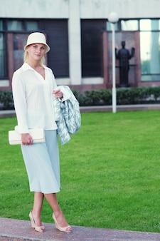 Młoda moda blond kobieta spacerująca po ulicy