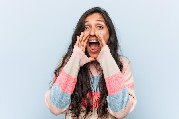Młoda moda indyjska kobieta krzyczy podekscytowany do przodu.