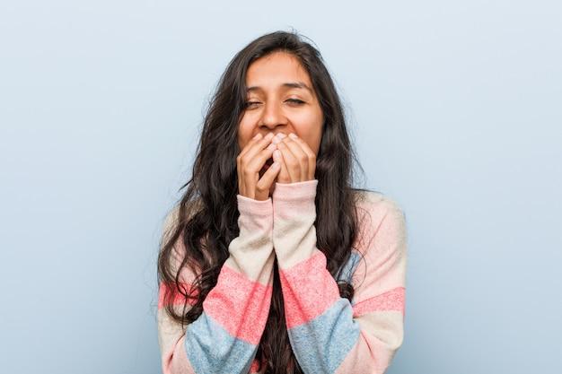 Młoda moda indyjska kobieta śmiejąc się z czegoś, obejmujące usta rękami.