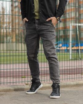 Młoda moda ma nogi z czarnymi trampkami czarne buty