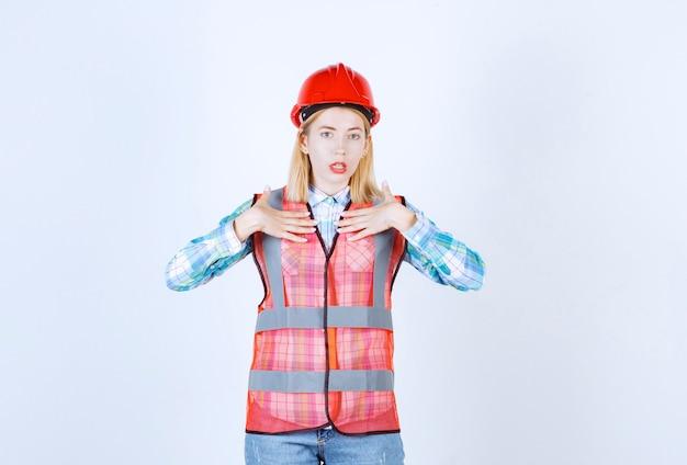 Młoda modelka blondynka kładzie rękę blisko jej klatki piersiowej przed białą ścianą
