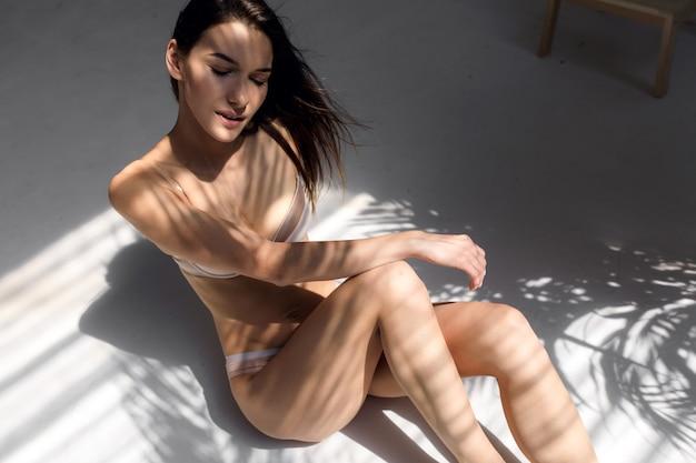 Młoda modelka ciesząca się słonecznym porankiem dziewczyna z piękną figurą w bieliźnie cieszy się słońcem