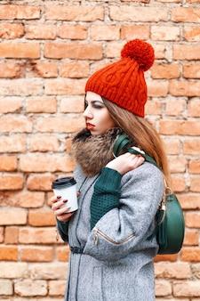 Młoda modelka dziewczyna pozuje z torbą kawy i ciepłe zimowe ubrania w pobliżu czerwonego muru z cegły