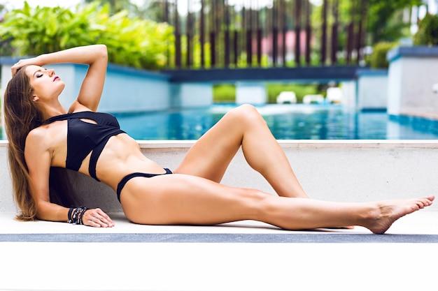 Młoda modelka fitness do opalania leżała na podłodze, luksusowa moda w minimalistycznym stylu