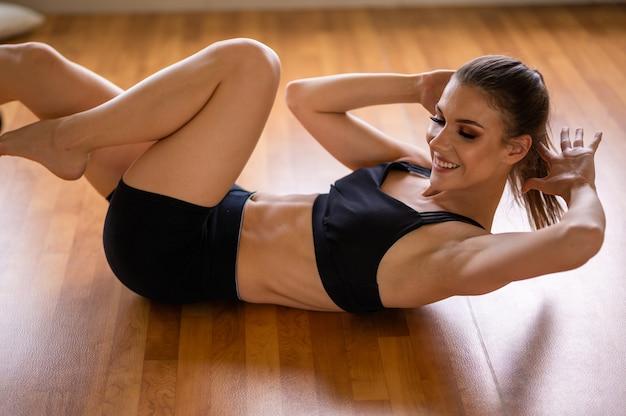Młoda modelka fitness stoi na siłowni naprzeciwko lustra wysokiej jakości zdjęcie