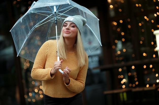 Młoda modelka jesień z parasolką w deszczu na ulicy w żółtym swetrze